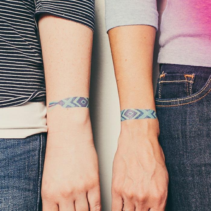 idea de tatuajes iguales para parejas, tattoos pequeños, brazalete de color morado y tonos azules en la muñeca, mujer y hombre en jeans