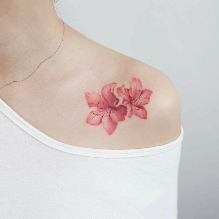 tatuaje hombro, tatuaje femenino en la clavícula, flor de hibisco en rosado, mujer con blusa branca de hombro caído