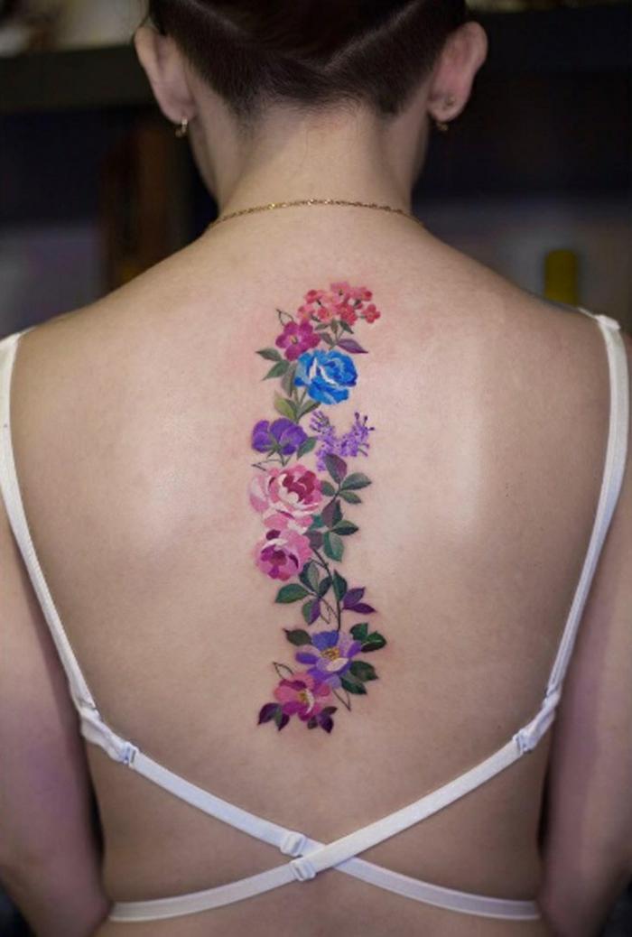 tatuaje espalda, tatuaje femenino grande de acuarela, corona de flores que cubre la columna vertebral, azul, morado y rosado