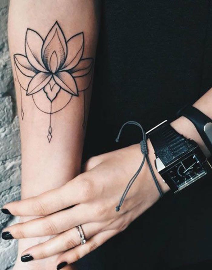 flor de loto tatuaje, mujer con esmalte negro, tatuaje en el antebrazo, flor de loto abierta en blanco y negro, reloj y pulsera
