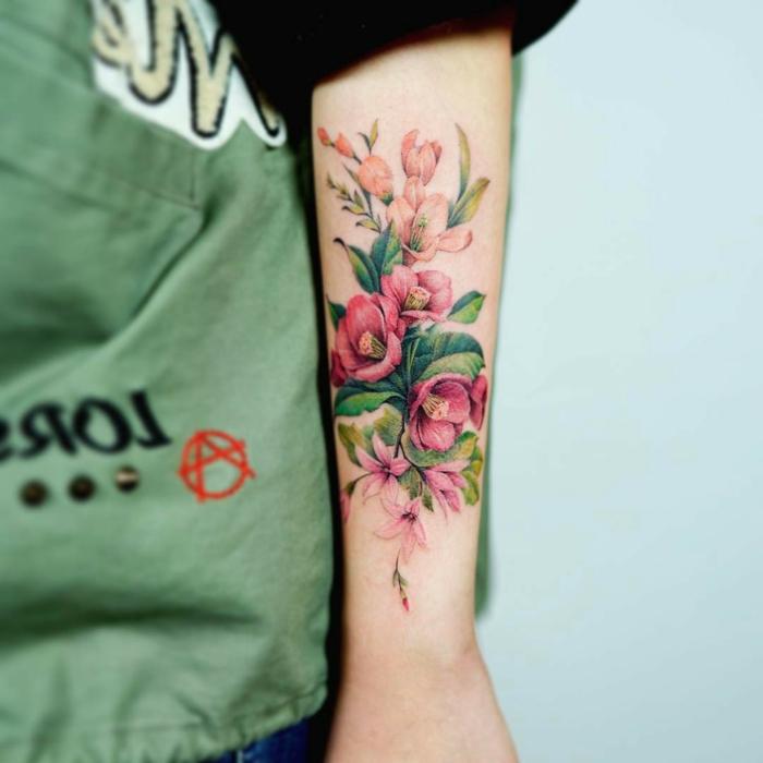 tatuajes flores, mujer con tatuaje en el antebrazo, ramo de flores en rosado con hojas verdes, tatuae grande