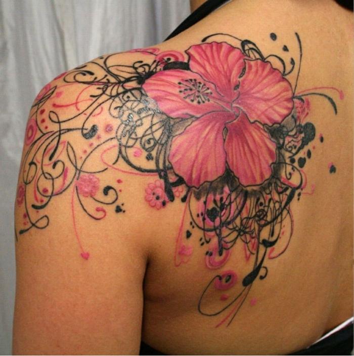 tatuaje espalda, mujer con tatuaje grande, flor hawaiana en negrpo y rosado en hombro y espalda, adornos adicionales