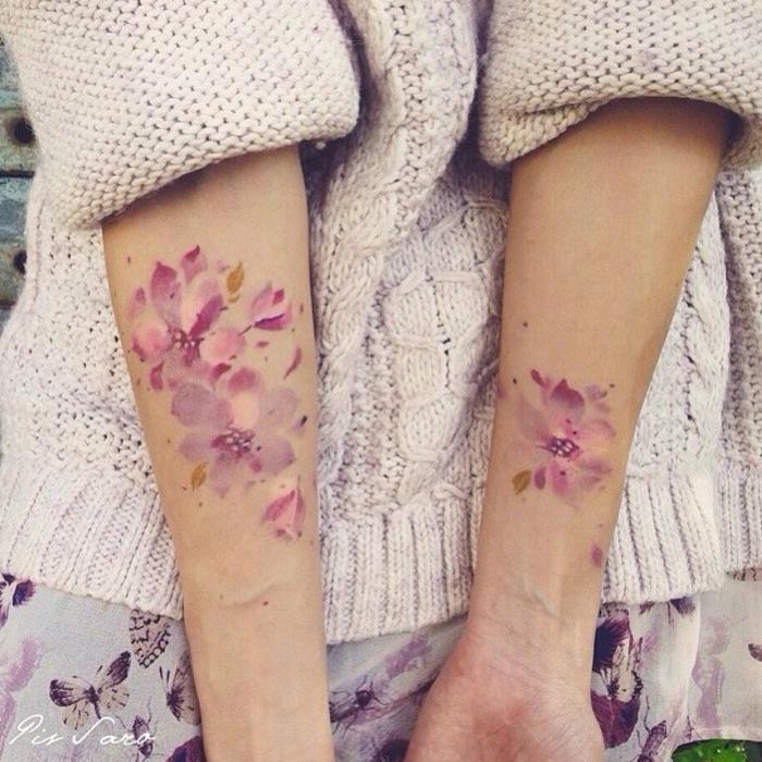 tatuajes flores, mujer en rosado con jersey, tatuaje femenino en los dos antebrazos, estilo acuarlea, flores en rosado