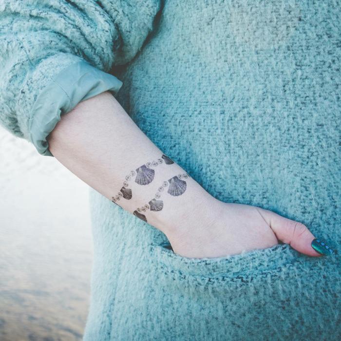 mujer con jersey aguamarina, tatuaje brazalete en la muñeca con cocnchas de mar en dos, uñas pintadas de verde metálico, tatuajes originales
