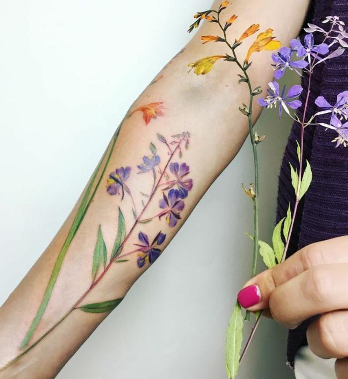 tatuaje muñeca, flores campanulas en morado y amarillo, tatuaje femenino en el antebrazo, estilo acuarela, mujer con uñas ciclamen