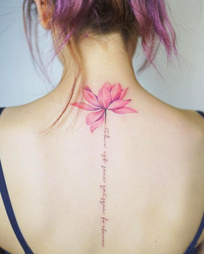 tatuaje flor de loto, mujer con pelo morado recogido, tatuaje con flor rosado y tallo de frase en cursiva en la línea de la columna vertebral