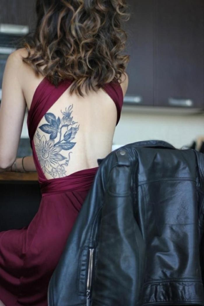 tatuaje flor de loto, mujer en vestido color vino con espalda descubierta, tatuaje en la espalda, girasol y planta carnívora en blanco y negro