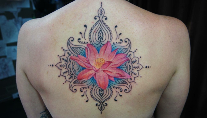 flor de loto tatuaje, espalda de mujer, tatuaje grande nde flor de loto ro\sada abierta en fondo azul, adornos con motivos hindus