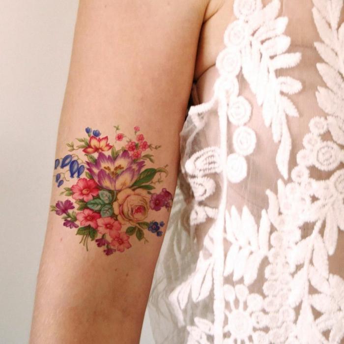 tatuaje acuarela, mujer con blusa blanca, tatuaje femenino en el brazo, ramo de flores con campanulas, rosas, lirios