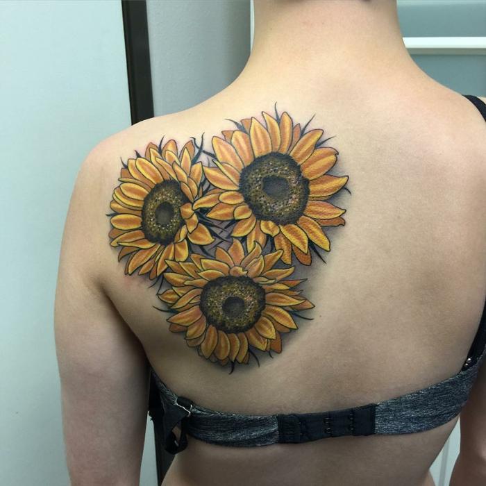 tatuajes flores, tatuaje grande en la espalda de mujer, tres girasoles de color con efecto 3D