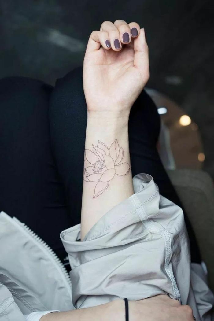 tatuajes de flores, mujer con uñas en morado, tatuaje pequeño en blanco y negro, antebrazo, flor de loto abierta
