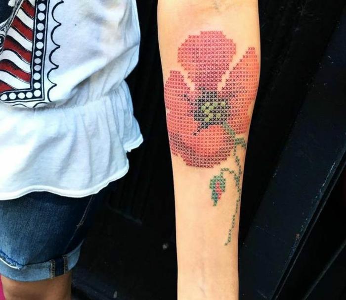 tatuaje muñeca, mujer con pantalones cortos, tatuaje en el antebrazo, amapola grande con tallo verde, imágen con efecto de pixeles