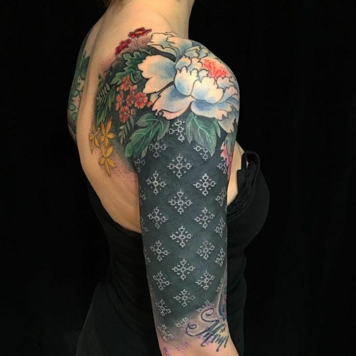 tatuaje espalda, mujer con tatuaje grande en brazo, hombro y espalda, fondo negro, dalia grande blanca, nombre en cursiva