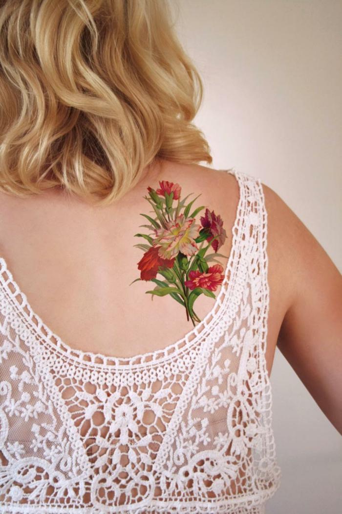 tattoos pequeños, mujer con pelo rubio, tatuaje en la espalda, ramo de claveles realista con hojas verdes
