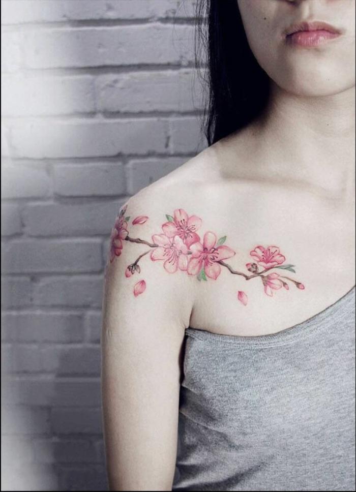 tatuaje hombro, mujer flaca con blusa gris, tatuaje de flor de cerezo en hombro y clavícula, color rosa