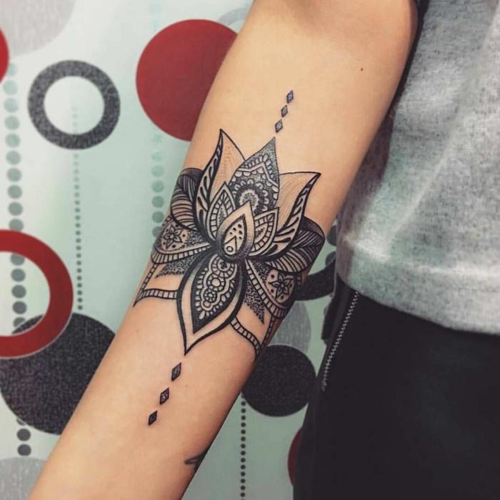 tatuaje pequeño, tatuaje en el antebrazo de mujer, flor de loto con motivos orientales en blanco y negro, tatuaje brazalete