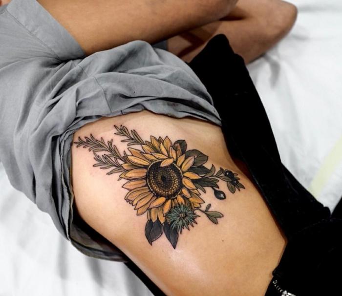 tatuaje espalda, cuerpo de mujer, tatuaje grande de color con girasol y aceitunas, tatuaje en el torso, blusa gris