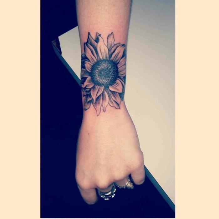 tattoos pequeños, tatuaje pequeño para la muñeca, girasol en blanco y negro, amno de mujer con anillos