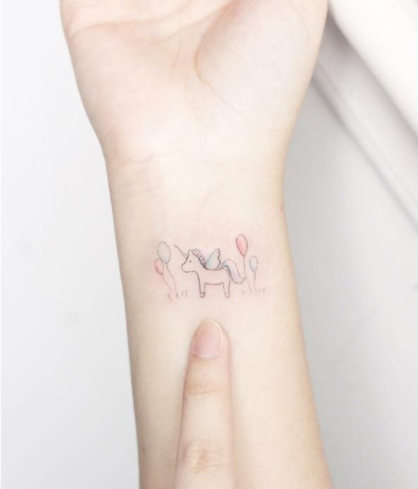 tatuaje para mujeres con dibujo infantil de unicornio con globos, colores pálidos rosado y azul, tatuajes flechas, diseño minimalista