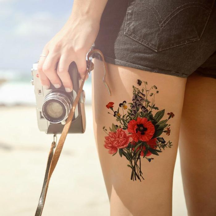 tatuajes flores, mujer fotógrafa, tatuaje con colores fuertes en la cadera, ramo de flores con amapolas rojas y campanulas
