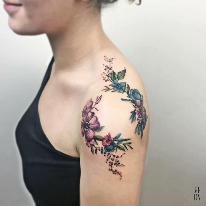 tatuaje hombro, mujer con blusa negra y pelo recogido, tatuaje con coronas de flores en morado y azul alrededor del hombro