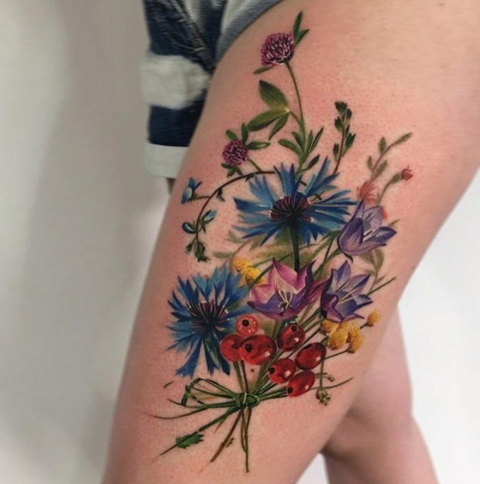 tatuajes flores, mujer con tatuaje grande en la cadera, ramo de flores con margaritas, campánulas y rosa de mosqueta
