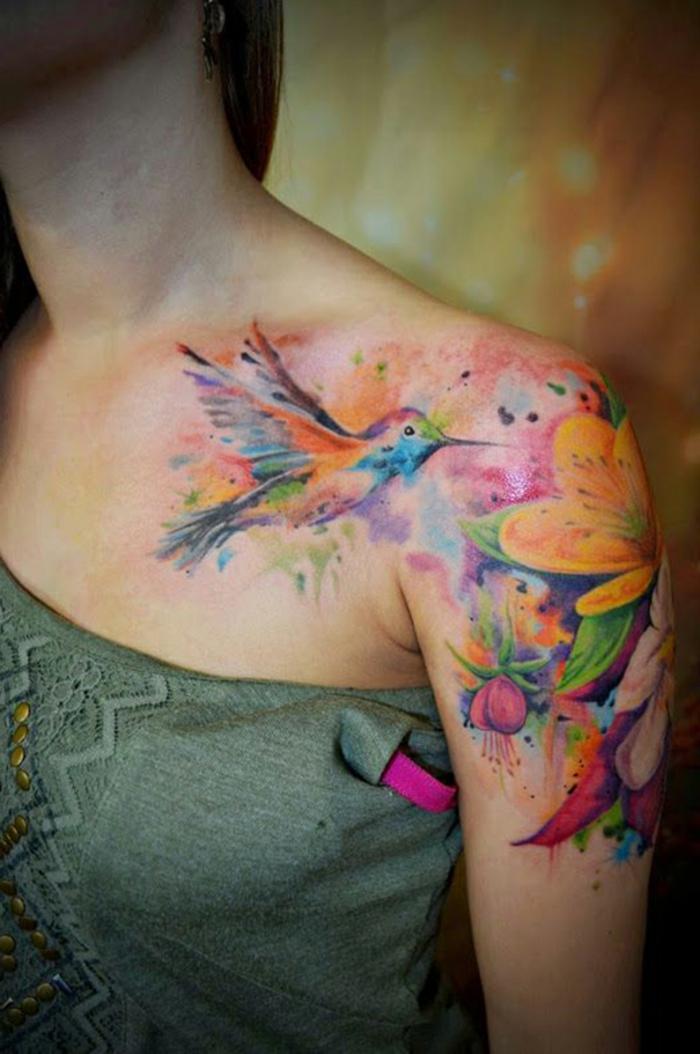 tatuaje hombro, tatuaje grande con efecto acuarela, mujer con clavícula y brazo tatuados, flores hawaianas y colibrí