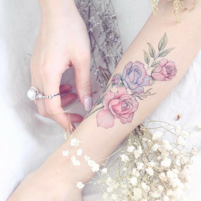 tatuajes acuarela, mujer con esmalte y anillos con perlas, tatuaje antebrazo, rosas en rosado y morado