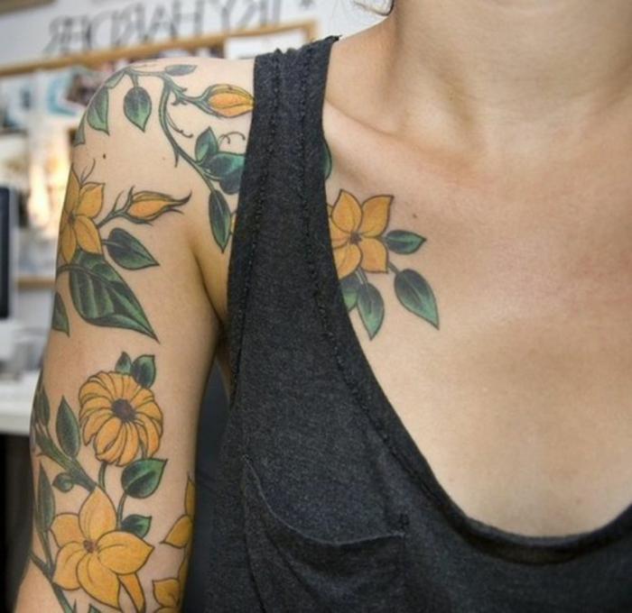 tatuaje hombro, mujer flaca con tatuaje grande en el brazo y el hombro, flores amarillos con tallos y hojas verdes