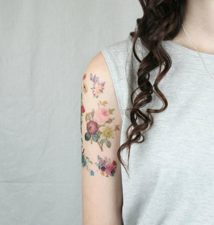 tatuaje ho,mbre, tatuaje femenino en el brazo, ramos de flores de diferente tamaño, mujer con cabello largo y blusa gris