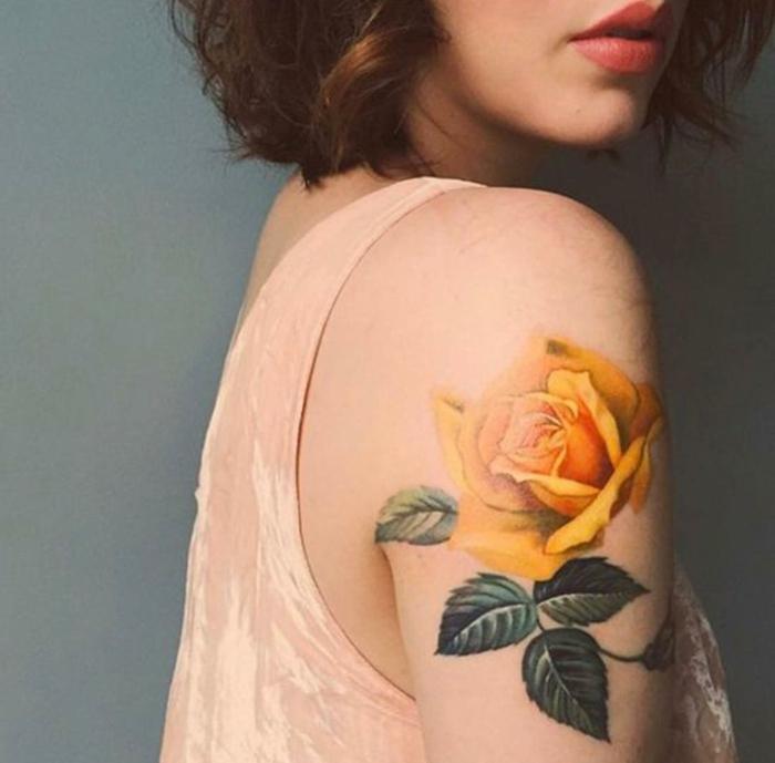 tatuaje hombro, mujer con tatuaje grande realista en el brazo, rosa amarilla con tallo y hojas verdes