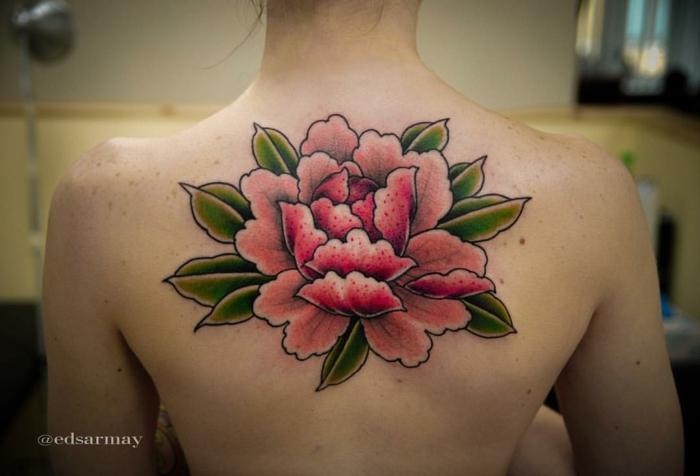 tatuaje acuarela, mujer delgada, piel con lunares, espalda con tatuaje grande, flor de loto rosada con hojas verdes