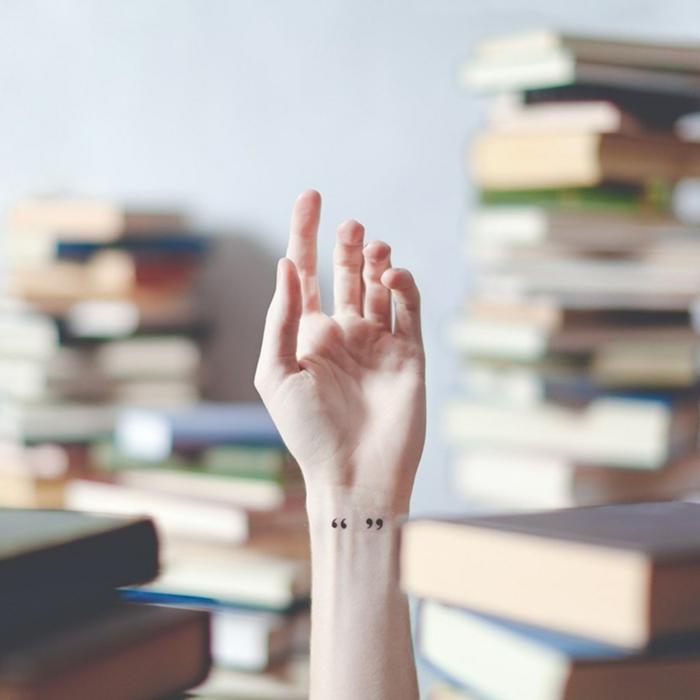foto artística, mano con tatuaje de comillas en la muñeca, tatuajes flechas, fondo desenfocado con libros
