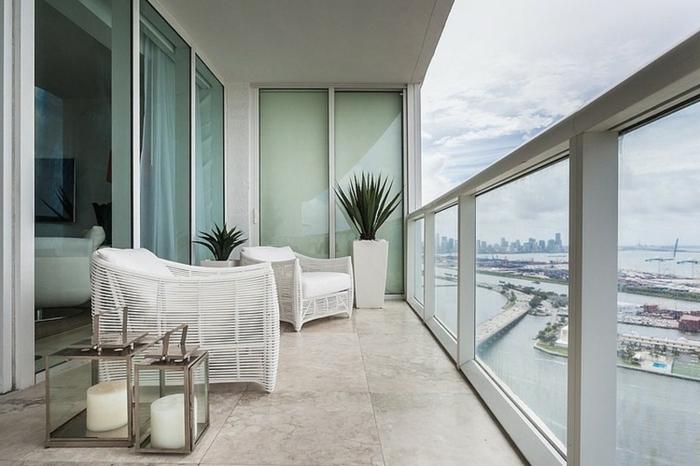 como decorar una terraza en blanco, bonita terraza con vista decorada con plantas verdes y velas decorativas, muebles de diseño original
