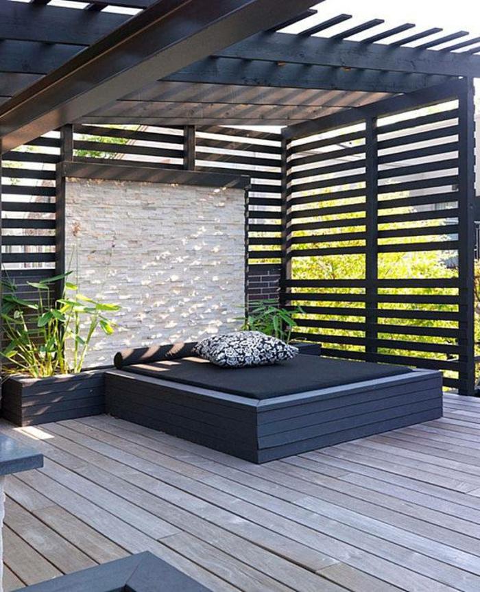 diseño sencillo y moderno de una terraza con grande cama en negro, suelo de madera, pérgola moderna pintada en negro