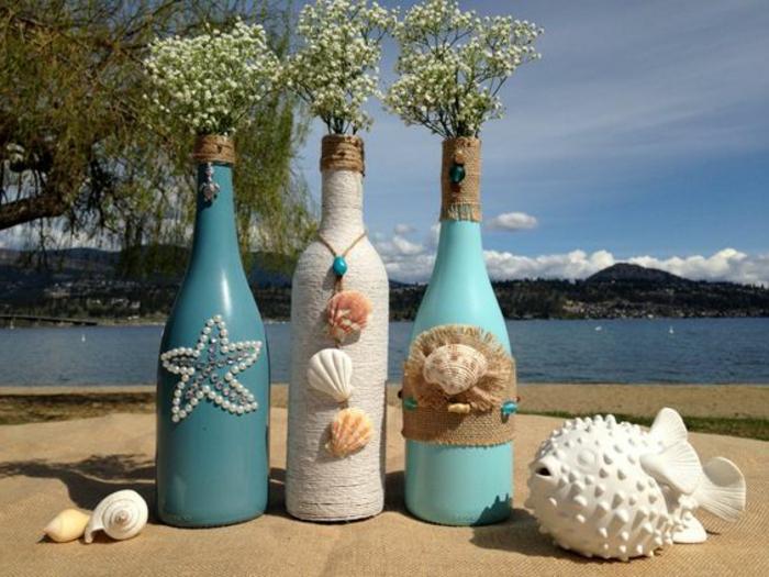 bonita propuesta para jarrones DIY, ideas con botellas de vino recicladas, botella de agua dibujo decorada con conchas e hilo cañamo