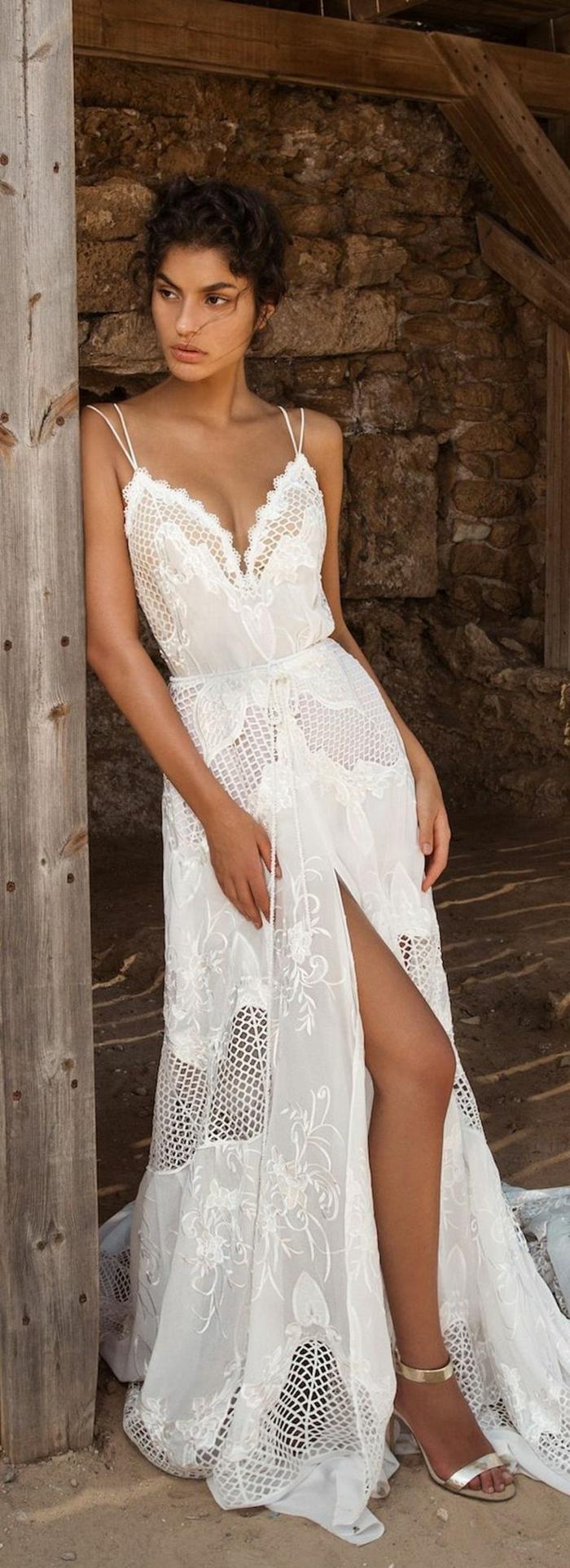 vestidos de novia ibicencos, mujer morena, vestido largo de encaje con hendidura, escote profundo, correas dobles, sandalias con tacón