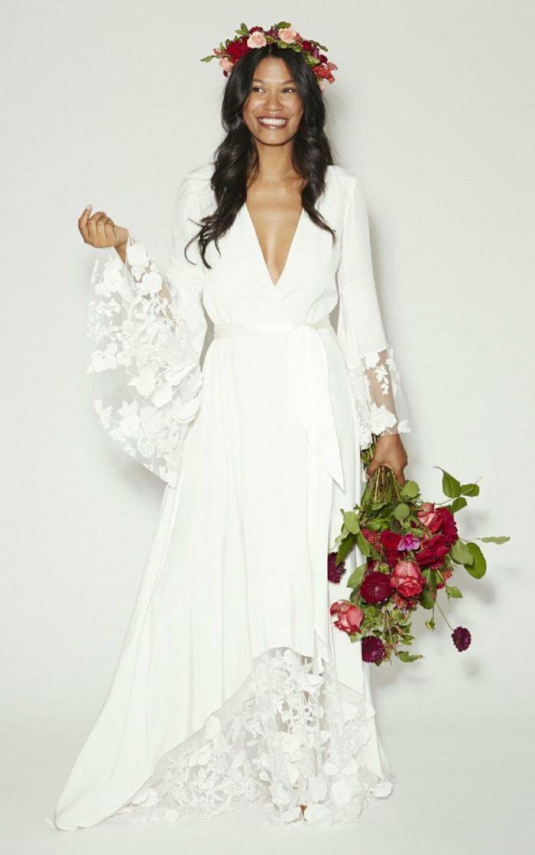 vestidos de novia ibicencos, vestido asimétrico con mangas largas, encaje guipur, escote V profundo, mujer con corona y ramo de flores