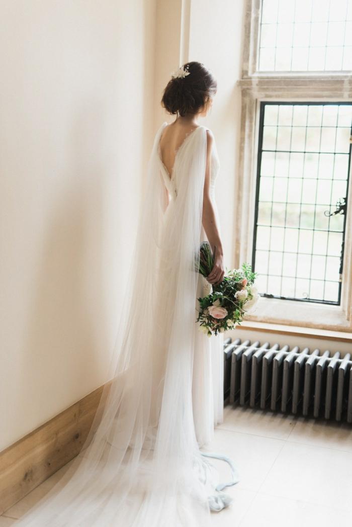 vestidos de novia modernos, vestido simple de corte princesa, peo recogido con grande velo, ramo de flores bonito