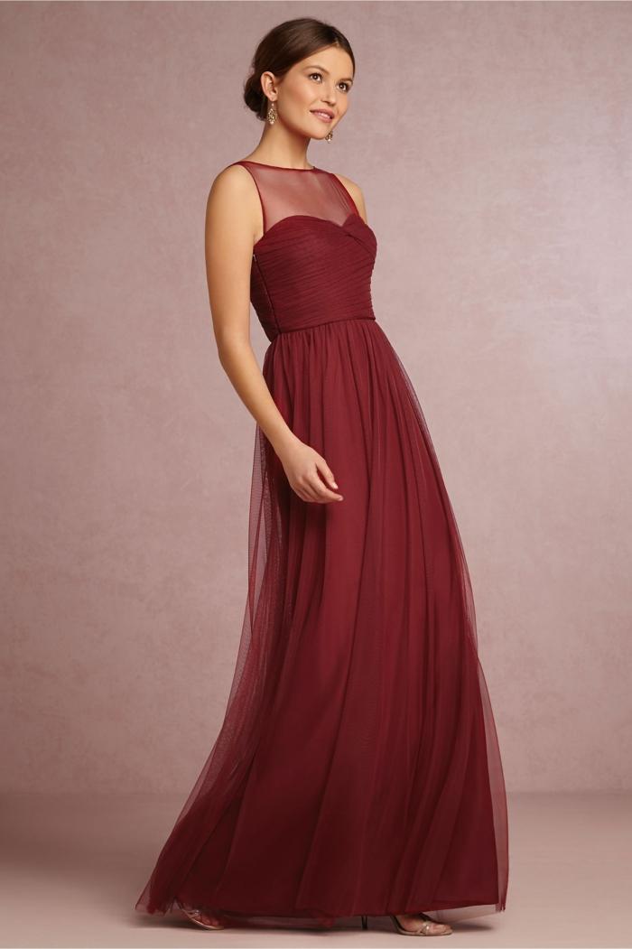 trajes de madrina, vestido largo elegante de color vino sin mangas, cintura imperio. escote ilusión, mujer con pelo recogido bajo
