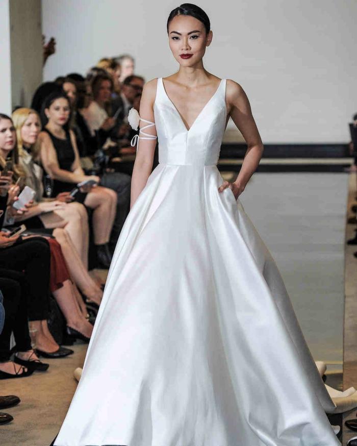 vestidos de novia pronovias, vestido de corte princesa con ornamento floral en el brazo, escote en V y pelo recogido en moño apretado