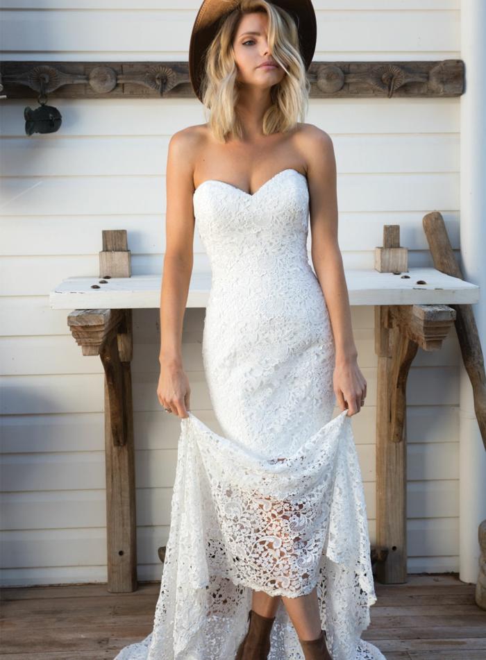 vestido blanco ibicenco, mujer con vestido largo con encaje, escote corazón, botas de piel, sombrero, media melena rubia