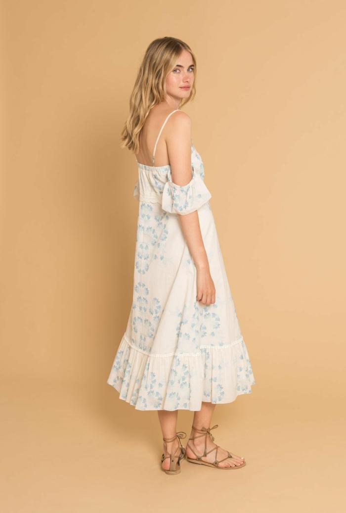 vestido ibicenco, mujer con pelo rubio suelto, vestido romántico en blanco y azul, hombros descubiertos, correas, sandalias romanas