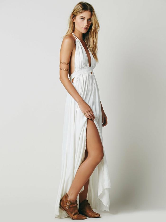 moda ibicenca, mujer con vestido blanco largo con hendiduram espalda descubierta, escote profundo, botas de piel