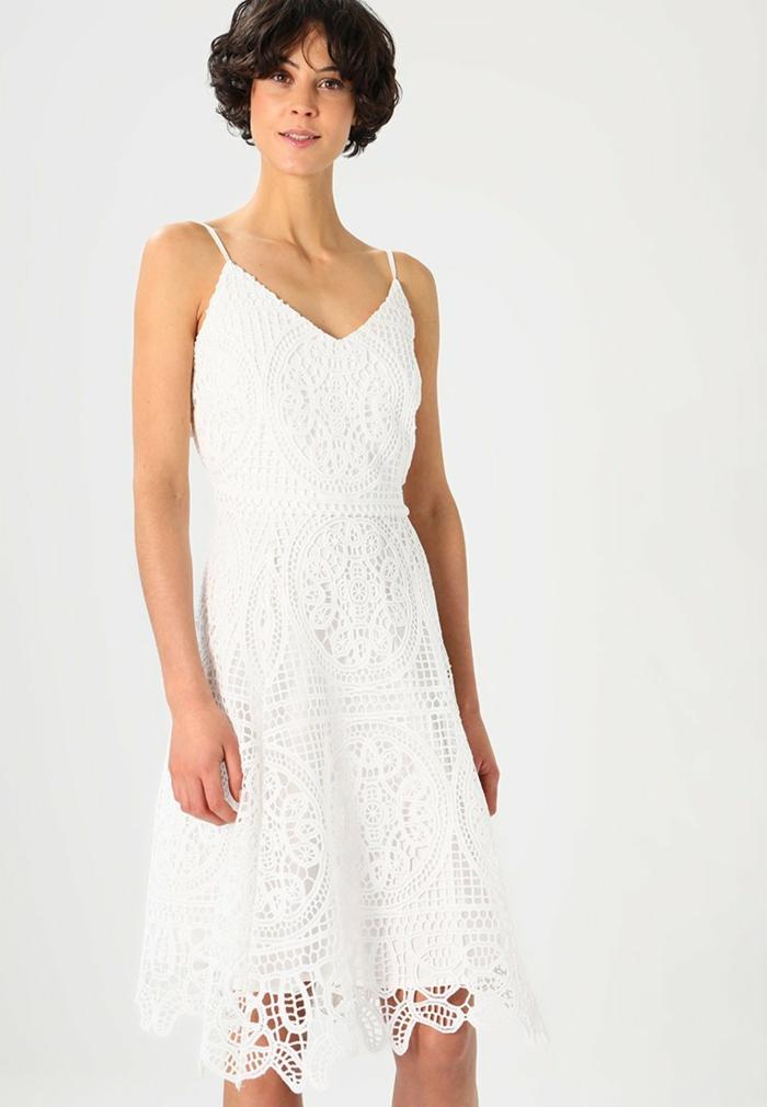 moda ibicenca, mujer con vestido blanco corto de encaje, tall princesa, escote V, correas delgadas, pelo corto negro