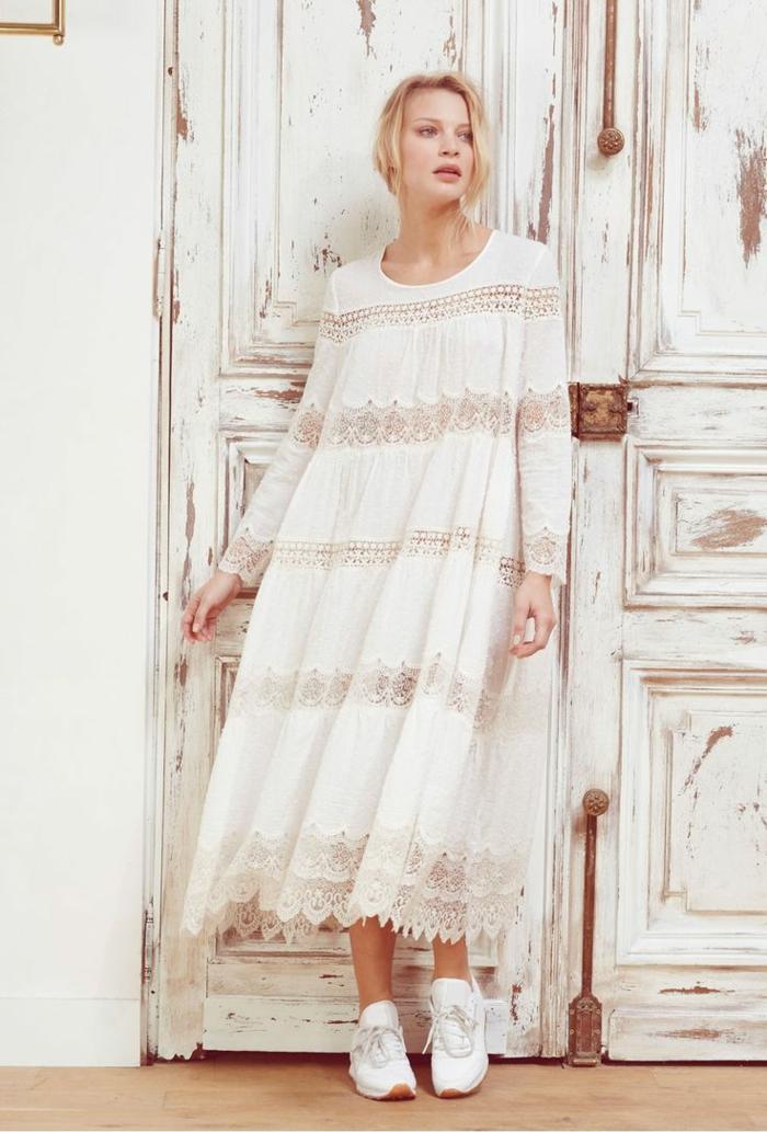moda ibicenca, mujer con zapatillas, vestido ancho largo con mangas largas y encaje, escote redondo, pelo recogido, puerta de madera con aspecto vintage