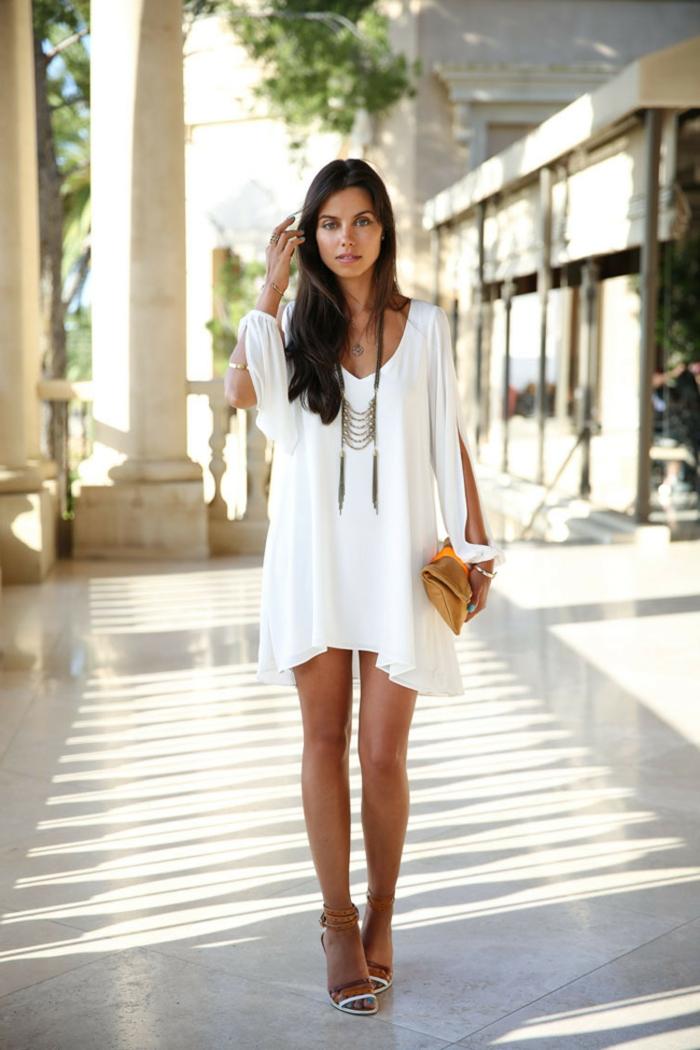 moda ibicenca, mujer con sandalias de tacón, vestido corto asimétrico, escite V, mangas largas abiertas, bolsa amarilla