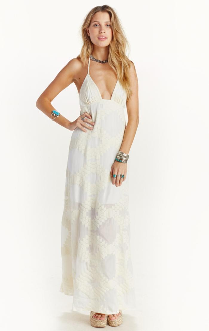 vestidos de novia ibicencos, vestido blanco largo con bordados en amarillo, con correas y escote profundo, mujer con collar y pulseras