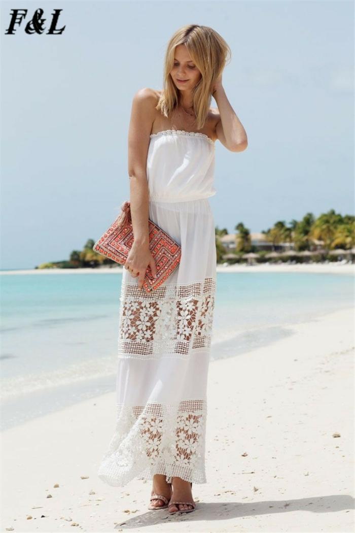 vestido ibicenco, mujer en la playa, vestido con escote palabra de honor, sin mangas, falda con encaje, bolsa con piedras decorativas