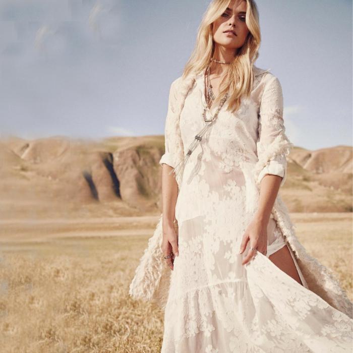 vestido ibicenco, mujer en una plata con vestido largo beige con bordado, hendidura, pelo rubio suelto, collar largo
